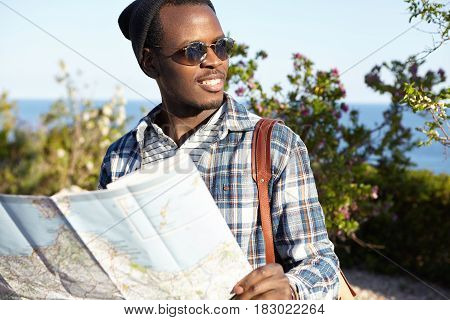 Youth, Lifestyle And Travelling. Dark-skinned Male Traveler In Sunglasses And Backpack Holding Road