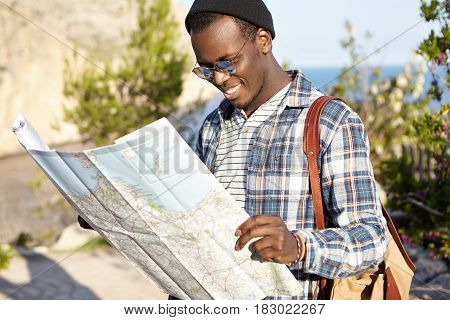 Outdoor Shot Of Happy Smiling Young Attractive African Tourist In Picturesque Landscape Reading Pape