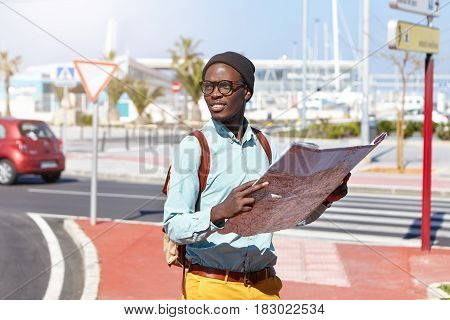 Happy Excited Dark-skinned Tourist Dressed In Stylish Clothes Walking Around Metropolis With Paper M