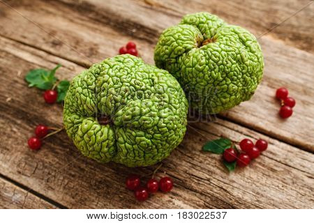 Top view on green exotic fruits with red berries. Osage apples or Maclura pomifera with viburnum and leaves on old grungy wooden table, bright sumer composition