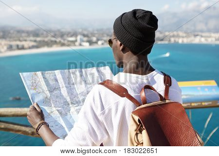 Outdoor Back Shot Of Dark-skinned Tourist With Leather Backpack On His Shoulders Holding Paper Guide