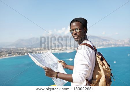 Portrait Of Young African American Traveler Looking At Camera With Paper Map In His Hands, Wearing S