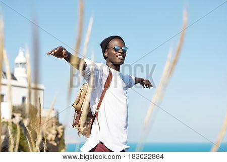 Cheerful Stylish Young African American Traveler With Backpack Smiling Joyfully, Spreading His Arms,