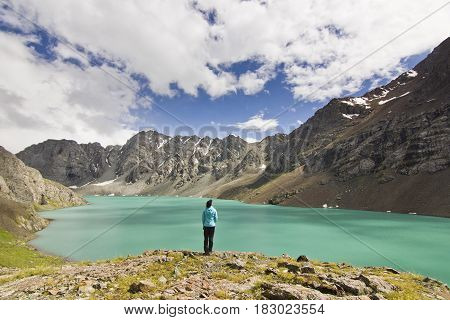 girl in blue jacket standing above blue calm mountain lake Alakol with mountains surrounded