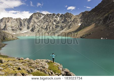 girl in blue jacket standing with hands up above blue calm mountain lake Alakol with mountains surrounded