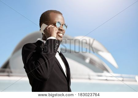 Happy Cheerful Black Businessman In Formal Wear And Sunglasses Talking On Smart Phone Outside Office