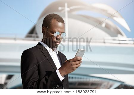 Elegant Serious African American Employee On Business Trip Checking E-mail On Mobile Phone, Standing