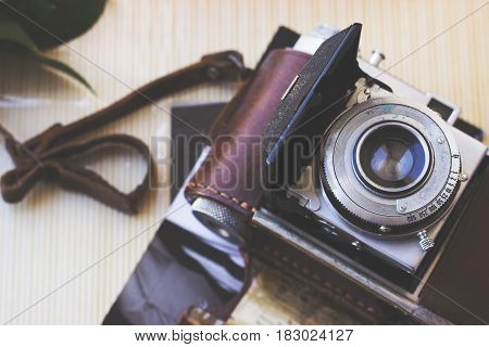 Old retro camera on aged photo album - abstract background