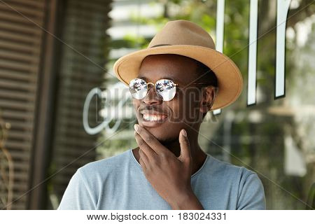 Close Up Portrait Of Happy Young Dark-skinned Male Tourist Sitting At Sidewalk Cafe, Touching His Ch