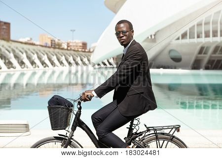 Confident African American Businessman In Formal Wear Commuting To Work On Black Bicycle. Corporate