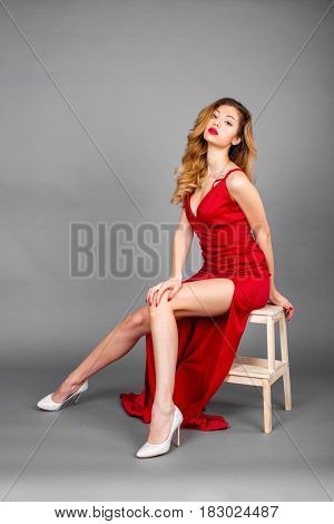 Fashionable pretty sexy young blonde woman sitting on a stool posing on gray wall background