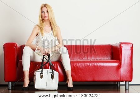 Fashion clothes clothing accessories trendy outfits concept. Woman wearing light outfit and black high heels sitting on red sofa holding white bag