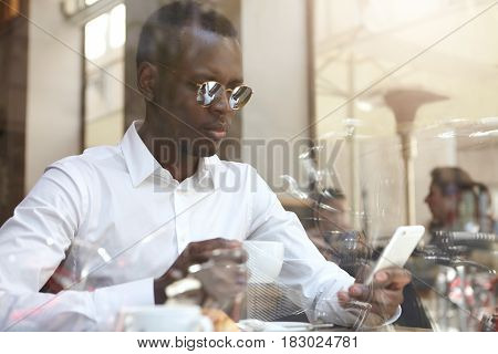 View Through Window Glass Of Handsome Black Bisunessman Or Corporate Worker Wearing Round Shades And