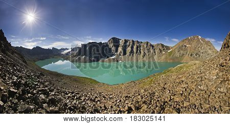 panorama of blue calm mountain lake Alakol with stones on shore and clouds on blue sky in tian-shan mountains at sunrise