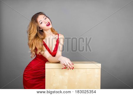 Fashionable pretty sexy young blonde woman stands behind a small table posing on gray wall background