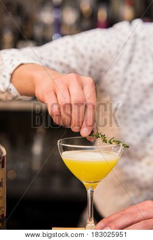 Closeup of barman hand putting on a glass to prepare cocktail.