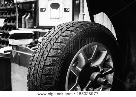 Wheel in a balancing tire changer in a black and white image