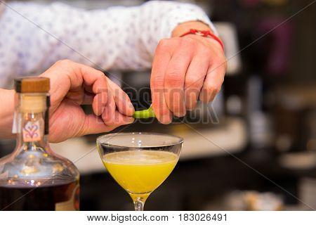 Closeup of barman hand putting lemon peel on a glass to prepare cocktail.