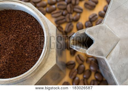 Ground coffee in vintage moka pot. Coffee beans around on table. Shallow depth of field.