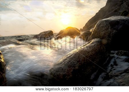 sea sprays on a cliff at the sunset