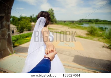 A beautiful young woman, the bride holds the hand of the man in the open air in the park. Follow me. Romantic.