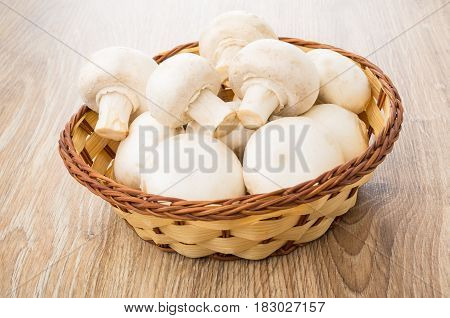 Wicker Basket With Mushrooms On Wooden Table