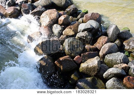 Small sea waves beating against the stones