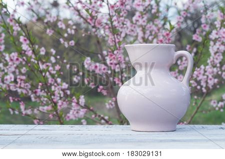 Porcelain pink jug on a table of white boards against the background of flowering bush