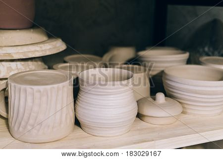 Handcrafted pottery on wooden shelf, ceramic handmade crockery in pottery workshop or studio