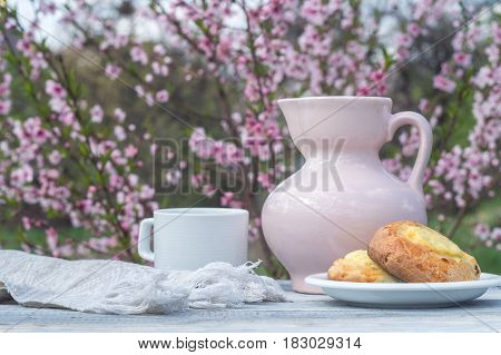 Porcelain pink jug, white cup and bakery on a table of white boards against the background of flowering bush