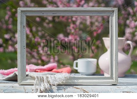 White frame, porcelain pink jug, cup and napkin on a table of white boards against the background of flowering bush