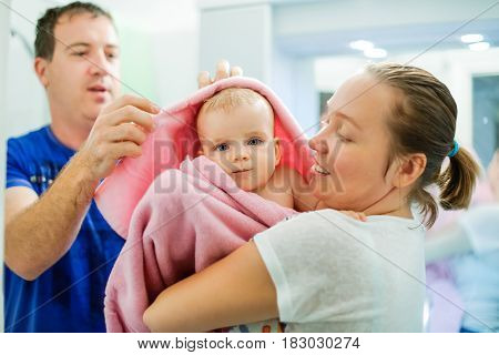 Happy Young Mother Holding Her Baby Wrapped In Pink Towel After Bathing By Father In The Bath Room.