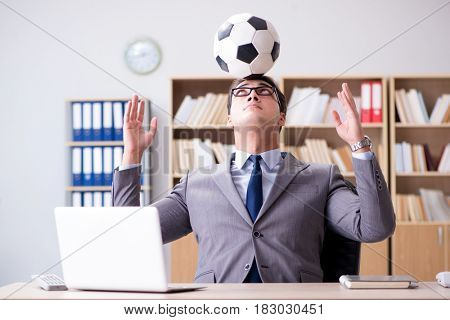 Businessman with football ball in office