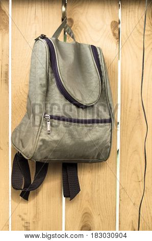 Bag (backpack) on wooden wall background. Education concept.