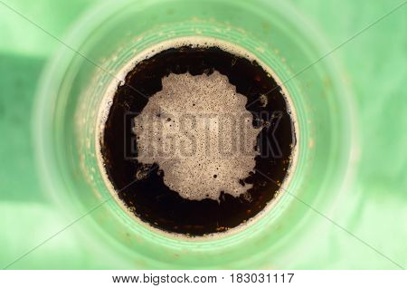 Dark beer (ale) in a plastic cup on the table. Top view. Outdoor vacation concept.