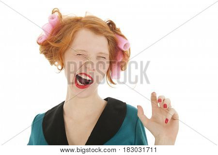 Young woman with curlers and lipstick yawning isolated in studio