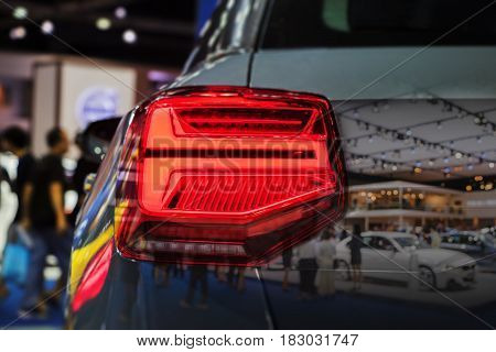 Double exposure Closeup Back Red Tail light car in Motor Show