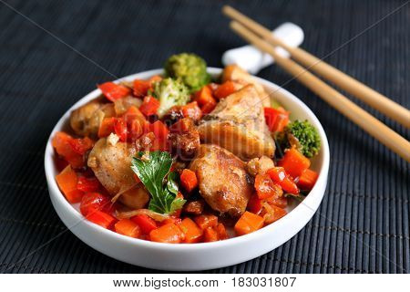 Chicken stir fry with vegetables and chopsticks on table