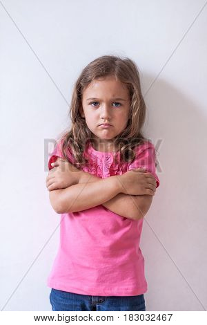 Portrait of Little Six-Year Sad Russian Girl With Expression Face In Pink T-Shirt On White Wall Background Close Up.
