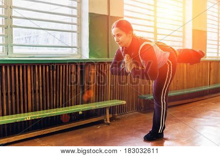 Young woman doing yoga poses in spot gym