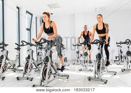 Group of fit people training at class. Cardio workout. Indoor cycling.