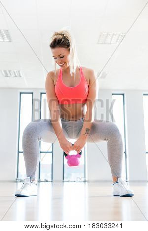 Fit woman doing a squat with kettlebell.  exercise session. Endurance and sport concept.