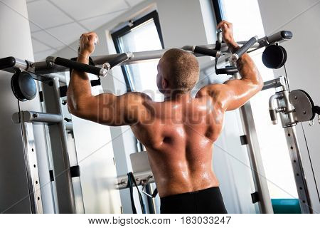 Muscular strong man working out at a gym. chinup training. Bodybuilding and fatburning.
