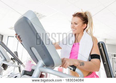 Young, smiling woman starts treadmill running in a gym. Sport and fitness concept.