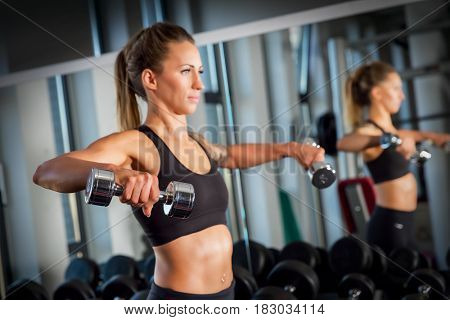 Young woman lifting dumbbells next to a mirror at a modern gym. Body training, weightlifting workout.