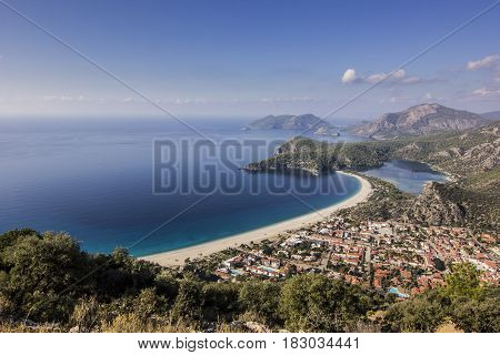 oludeniz bay in turkey with village near shore of blue sea and yellow beach with mountains