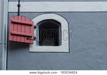 A renovated wall of a traditional house in the city of Riga. Latvia. There is a window with a shutter.
