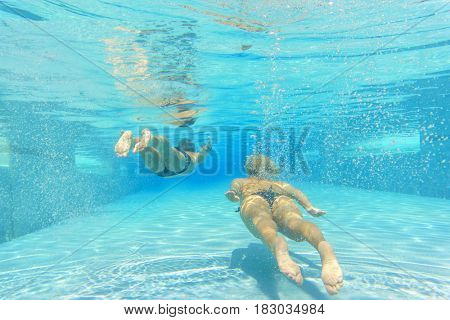 Underwater shot of the young couple in the pool