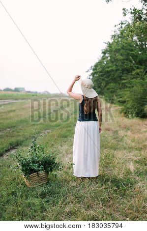 people, holidays and nature concept - beautiful woman in fancy clothes and elegant hat posing with back to us against rural fields and trees, on ground is basket with green branches for decoration .