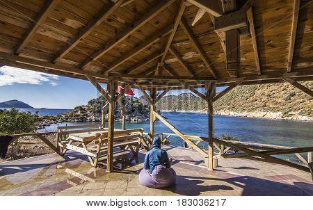 man in blue jacket sitting on ottoman in open veranda under the roof near mediterranean sea meditating